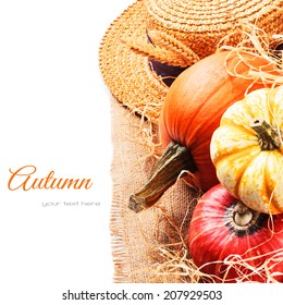 Autumn setting with harvested pumpkins and straw hat