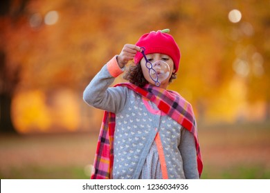 Autumn setting with Young girl blowing bubbles in the park
