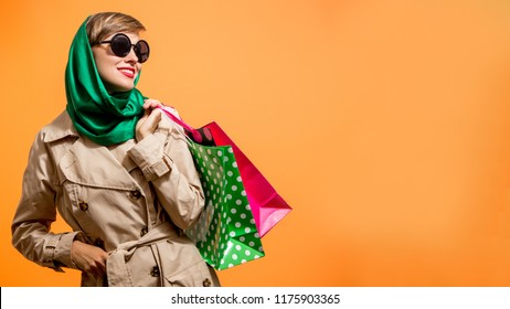 Autumn shopping woman holding shopping bags with autumn colors over bright orange background