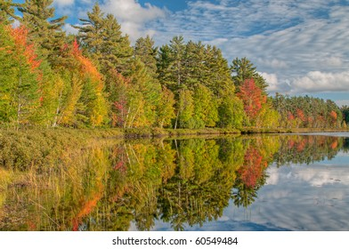 Autumn shoreline of Island Lake with reflections in calm water, Michigan's Upper Peninsula, USA