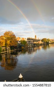 Autumn shower with double rainbow over a river in Holland