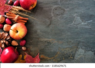 Autumn side border of apples, fall foods and decor on a dark stone background with copy space