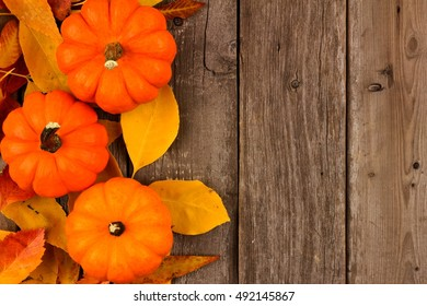 Autumn Side Border Of Pumpkins And Leaves Against A Rustic Old Wood Background