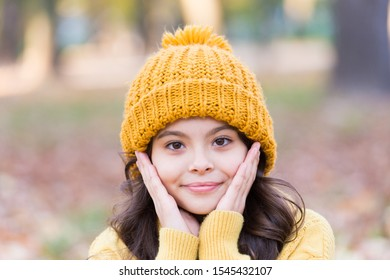 Autumn skin care. Little child wear hat on autumn landscape. Small girl touch clean pure skin. Organic cosmetics for skin. Natural beauty. Adapt kids skin for autumn weather.