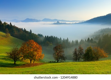 Autumn in Slovenia with fog. Saint Thomas Church, Sveti Tomaz nad Praprotnim, Skofja Loka. Foggy Alps with forest, travel in Slovenia, Europe. Beautiful sunrise with blue sky, green nature.