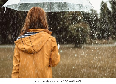 Autumn solitude. Woman standing with back turned and holding umbrella outdoors. She is strolling on her own enjoying wet weather. Copy space in right side