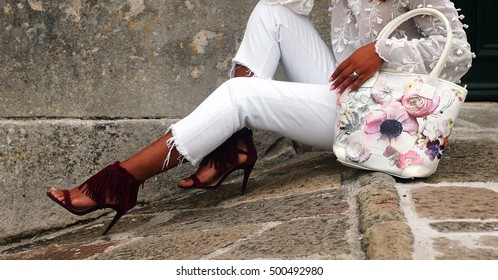 autumn or spring outfit - beautiful african italian girl wearing white jeans, white shirt, burgundy red gilet and high heels, and leather bag with floral prints