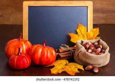 Autumn still life arrangement of pumpkins, nuts and yellow leaves around a blank vintage chalk board