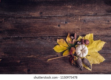 Autumn still life arrangement with yellow maple leaf, pumpkin, pine cone and chestnuts on a vintage wooden background. Table top view