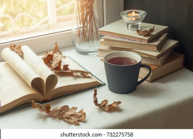 autumn still life. books, leaves, cup and candlestick on window. Concept of autumn reading time and romantic, hygge, unplug, mindfulness, Warm, cozy seat  opened book, rustic style home decor