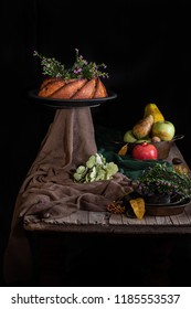 Autumn still life with bundt cake and seasonal fruit on old wooden table.