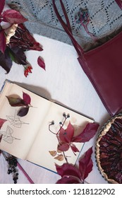 Autumn still life in burgundy colors. Autumn or winter concept, lifestyle blogers. Plum pie - flat lay, top view.