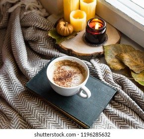 Autumn still life with coffee cup and candles, cozy fall interior details with blanket and coffee cup or hot chocolate
