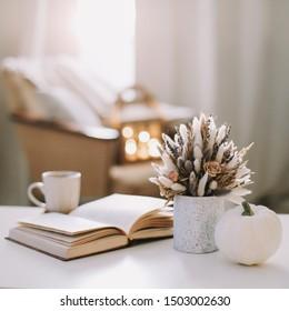Der Herbst ist noch lebendig. Kaffeetasse, Blumen, Buch und Kürbis. Hyge Lifestyle, gemütliche Herbststimmung. Flacher Laien, glücklicher Thanksgiving-Hintergrund