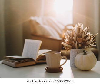 Autumn still life. Coffee cup, flowers, book and pumpkin. Hygge lifestyle, cozy autumn mood. Flat lay, Happy thanksgiving background