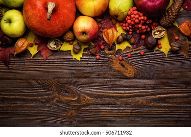 autumn still life decorated by pumpkins, fruit and gifts on wooden background