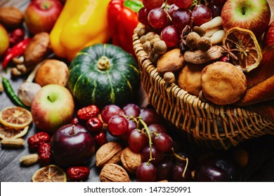Autumn still life. Different fruits and vegetables in the wicker basket on the wooden table: pumpkin, grape, garlic, apple, nuts, peanuts, drain, bell peppers,  hot pepper and dry lemon slices  table