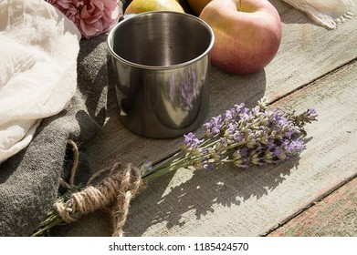 Autumn still life. Pear and apple on wooden table with a cup of red juice. Rustic design. Vintage concept in the garden.