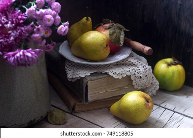 Autumn still life with pears, apple, chrysanthemums and books. Rustic style, selective focus.