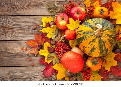 Autumn Still Life. Pumpkin, apples and yellow autumn leaves on the old board