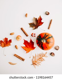 Autumn still life: pumpkin, leaves, cinnamon, chestnuts, acorns, candle on white background. Thanksgiving day frame. Copy space.Top view. Flat lay.