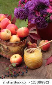 Autumn still life with ripe apples, asters, honey jar with deeper and autumn leaves. Russian religious holiday Spas still life