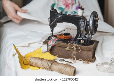 Autumn still life with a sewing machine. Vintage sewing machine and a skein of threads. A yellow maple leaf lies next to it. Behind the canvas with embroidery