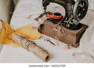 Autumn still life with a sewing machine. Vintage sewing machine and a skein of threads. A yellow maple leaf lies nearby