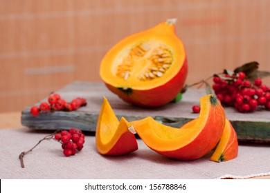 Autumn Still Life: sliced pumpkins and rowanberries.