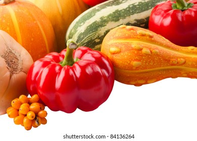 autumn still-life filled with vitamins from red paprika, pumpkin, vegetable marrows and ripe sea-buckthorn berries on isolated white background