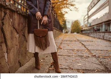 Autumn street fashion details: brown suede bag with fringe in hands of elegant woman wearing stylish outfit. Copy, empty space for text