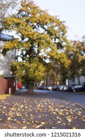 Autumn street image: fallen leaves on foreground; big tree, parked cars and one person in red jacket walking on background. Unfocused autumn mode.