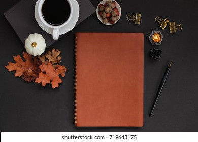 Autumn styled desk top in orange and black accents. Nature items, coffee, office supplies and blank leather binder cover for copy or text.