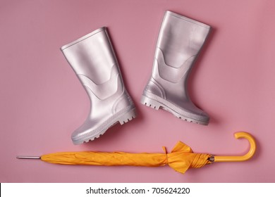 Autumn stylish set of silver gumboots and umbrella on pink background. Top view. Flat lay.