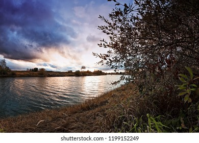 The autumn sun sets behind the river bend at the Northern Finland. The autumn colors are slowly fading away before the winter comes.