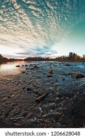 The autumn sun sets over the rocks on the river at the Northern Finland. Autumn colors are at their brightest.