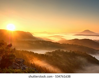 Autumn sunrise above above forest,  fall colorful valley full of dense mist colored with hot sun rays. Foggy strips between treetops between hills.