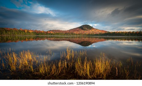 Autumn sunrise on Alford Pond in Lake Placid with water reeds in the foreground and a reflection of Mount Seymour in the background