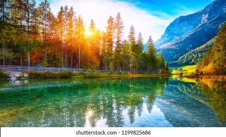 autumn sunset of Hintersee lake. Beautiful scene of trees near turquoise water of Hintersee lake. Location: resort Ramsau, National park Berchtesgadener Land, Upper Bavaria, Germany Alps, Europe