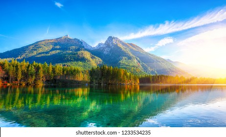 autumn sunset of Hintersee lake. Beautiful scene of trees near turquoise water of Hintersee lake. Location: resort Ramsau, National park Berchtesgadener Land, Upper Bavaria, Germany Alps, Europe