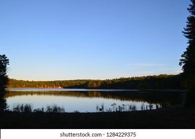 Autumn sunset on walden pond with reflection in the water.