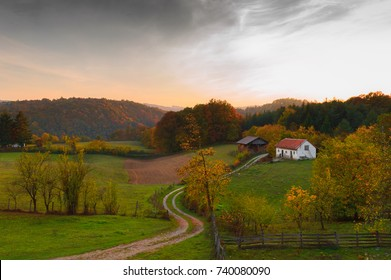 Autumn sunset.  Small farm landscape with curved road. Barn and stable.