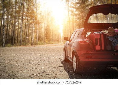 Autumn sunset time and car on road with suitcase