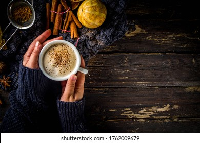 Autumn sweet hot drink, Chai Buttered Rum, Pumpkin Pie or Pumpkin Spice Coffee Latte. Cozy autumn background. Girl hold traditional latte cup in hands, on rustic wooden background
