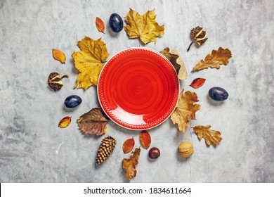 Autumn table setting composition. Empty red plate, cutlery, fresh plums, pumpkins, fallen leaves, acorns, chestnuts on a light background, top view, copy space. Autumn harvest , thanksgiving day