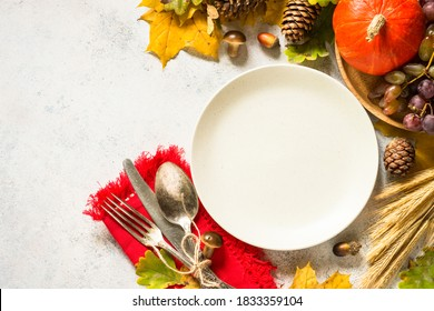 Autumn table setting with craft plate, silverware and fall decorations at white table. Thanksgiving food concept. Top view with copy space.