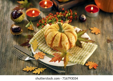 Autumn table setting with pumpkins and candles, fall home decoration for festive dinner