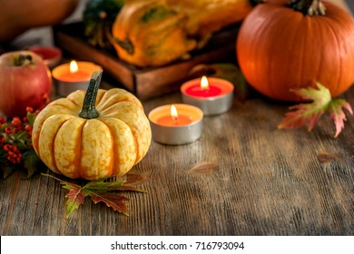 Autumn table setting with pumpkins and candles, fall home decoration for festive dinner copy space