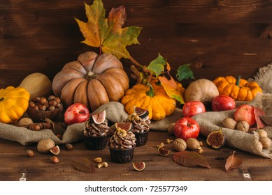 Autumn tasty cupcakes with ginger and chocolate on a wooden background of autumn harvest. Pumpkins, patsons, apples, nuts. toning