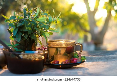 Autumn tea in black glass cup on old rustic linen napkin